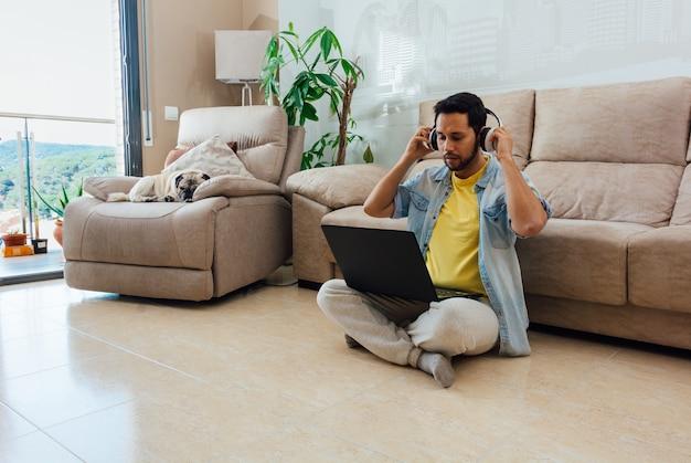 床に座って音楽を聴き、自宅でノートパソコンで作業している男性の水平方向のショット 無料写真