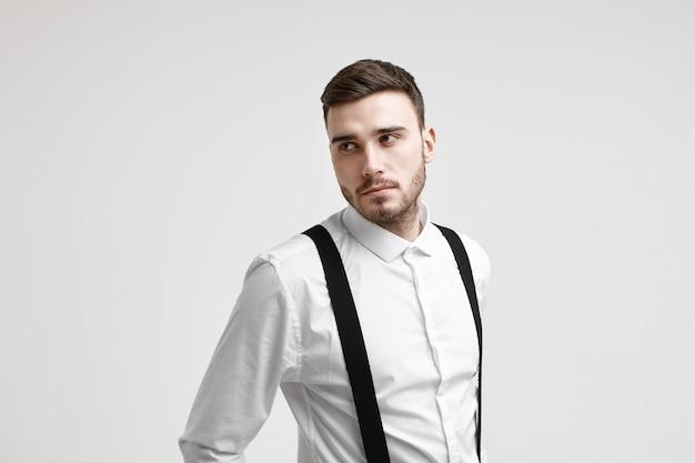 スタジオでポーズをとって、真剣な物思いにふける表情で脇を見て、ビジネスのアイデアや計画を考えて、エレガントなスーツを着た魅力的な若いひげを生やした白人従業員の水平方向のショット 無料写真