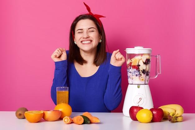 陽気な若い女性の水平ショットは、ミキサーでスムージーになります。肘を曲げて目を閉じて美しいブルネットは、おいしいフルーツカクテルを準備している間幸せそうです。健康的なライフスタイルのコンセプトです。 Premium写真