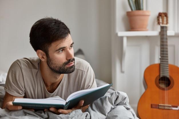 Горизонтальный снимок созерцательного кавказского парня с темной щетиной, в повседневной одежде, лежащего на кровати с книгой, одинокого дома, наслаждается выходными, ведет спокойную жизнь. домашняя атмосфера, концепция чтения Бесплатные Фотографии