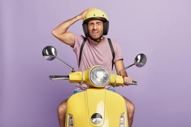 不機嫌な無精ひげを生やした男性ドライバーの水平方向のショットは、ヘルメットに手をかざし、速いバイクでポーズをとり、速く運転し、何かを運び、カジュアルな紫色のtシャツを着ています。人と輸送の概念 無料写真