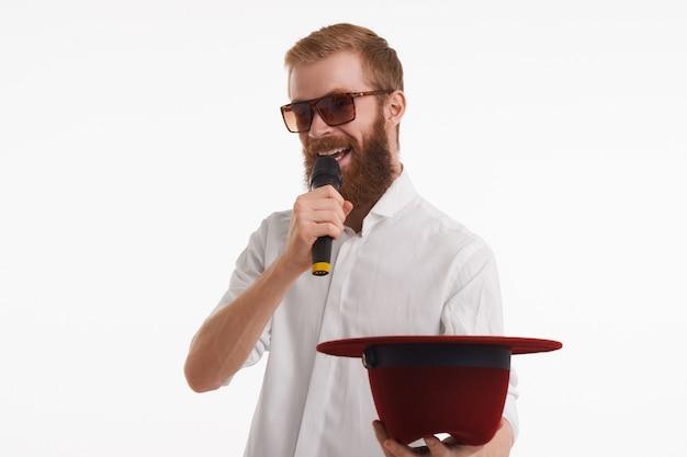 Горизонтальный снимок модного веселого молодого уличного артиста с пушистой рыжей бородой, говорящего в беспроводной микрофон и протягивающего руку, держащего шляпу, и просящего деньги в темных очках Бесплатные Фотографии