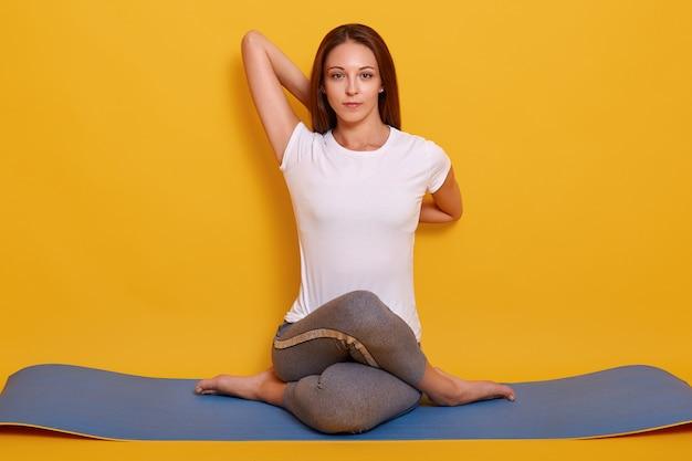 Горизонтальная съемка гибкой девушки делая представление йоги изолированное над желтым цветом Бесплатные Фотографии