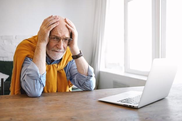 Горизонтальный снимок разочарованного старшего кавказского сотрудника-мужчины с седой бородой и очками, держащего руки на его лысой голове, с паническим взглядом и напряженным из-за крайнего срока. возраст и работа Бесплатные Фотографии