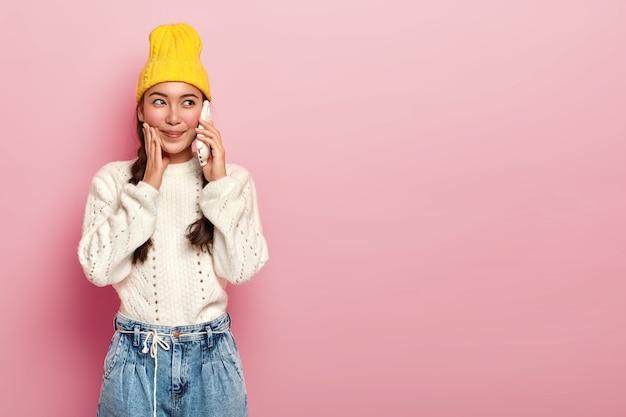 좋은 찾고 아시아 여자의 가로 샷 전화를 만들고, 캐주얼 옷을 입고 핸드폰을 통해 즐거운 이야기를 즐기고, 분홍색 배경에 실내 스탠드. 무료 사진