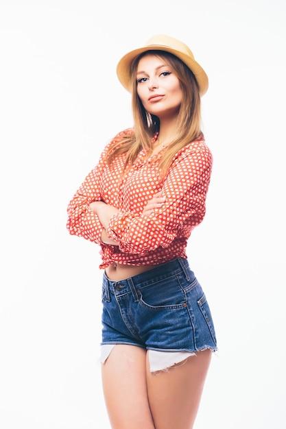 ゴージャスな女性モデルの水平方向のショットは、麦わら帽子に手を保ち、裸の肩で白いトップを着て、自信を持って表情で見え、白い背景の上に分離され、テキストのスペースをコピーします 無料写真