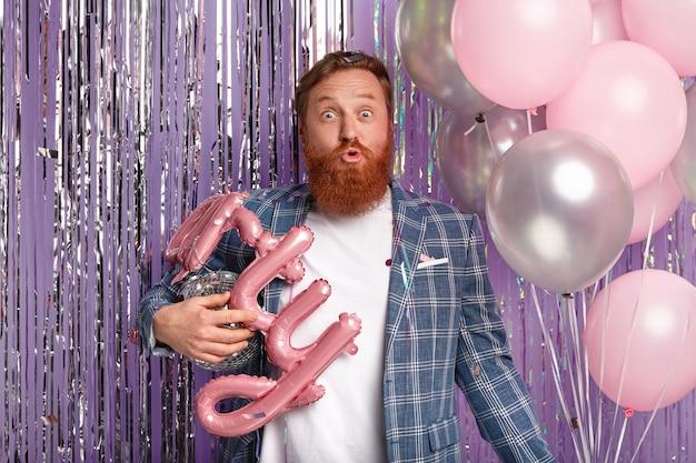 剛毛を持つハンサムな生姜男の水平方向のショットは、目を大きく開き、唇を折り畳み、気球を保持し、パーティーの装飾を準備し、エレガントな服を着て、屋内に立っています。お祝いのコンセプト 無料写真