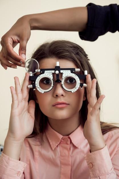 Горизонтальная съемка заинтересованной и любознательной кавказской девушки на встрече с phoropter специалиста ухода за глазами нося пока офтальмолог проверяя ее зрение, сидя над желтой стеной Бесплатные Фотографии