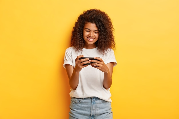 彼女の携帯電話でポーズをとって巻き毛のミレニアル世代の若い女性の水平方向のショット 無料写真