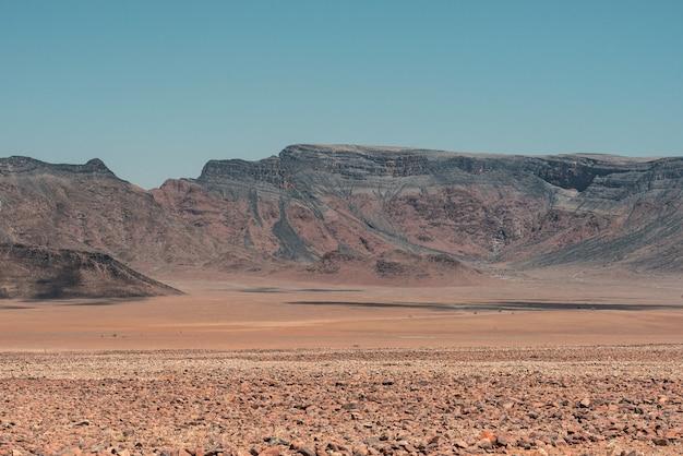 青い空の下でナミビアのナミブ砂漠の山の風景の水平方向のショット 無料写真