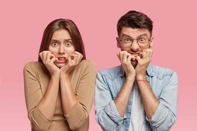 Горизонтальный снимок нервной молодой женщины и мужчины с тревожным выражением лица грызет ногти Бесплатные Фотографии