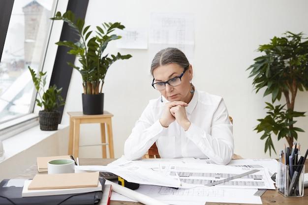 그녀의 앞에 책상에 도면과 사양을 공부, 그녀의 턱 아래 푹 손을 잡고 검은 안경과 흰색 셔츠를 입고 잠겨있는 중간 나이 든 여성 엔지니어의 가로 샷 무료 사진