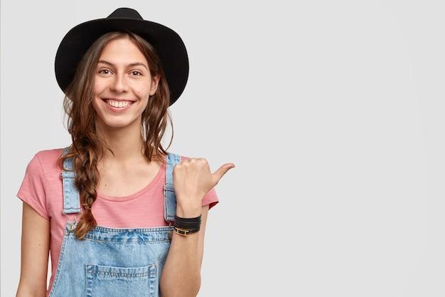 Горизонтальный снимок положительной женщины-хозяйки ранчо указывает на ее собственность, показывает сад с богатым урожаем, имеет счастливое выражение лица, носит элегантную черную шляпу, изолированную на белой стене с пустым пространством Бесплатные Фотографии