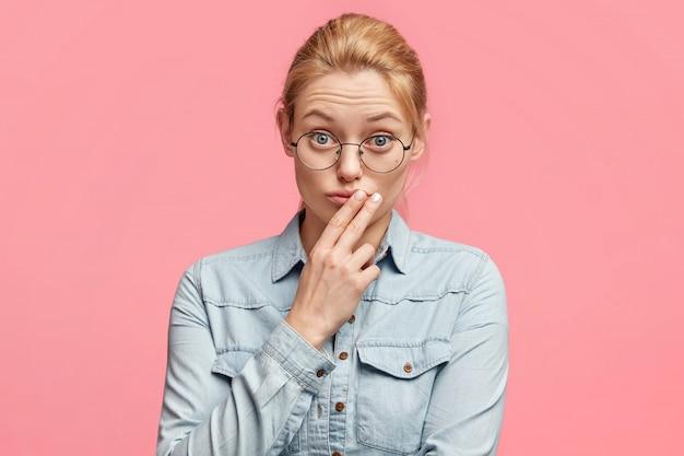 かなり明るい髪の女性の水平方向のショット、カメラに直接当惑し、丸い眼鏡をかけ、指を唇に付け続け、対話者に注意を向けて注意深く情報を聞く 無料写真