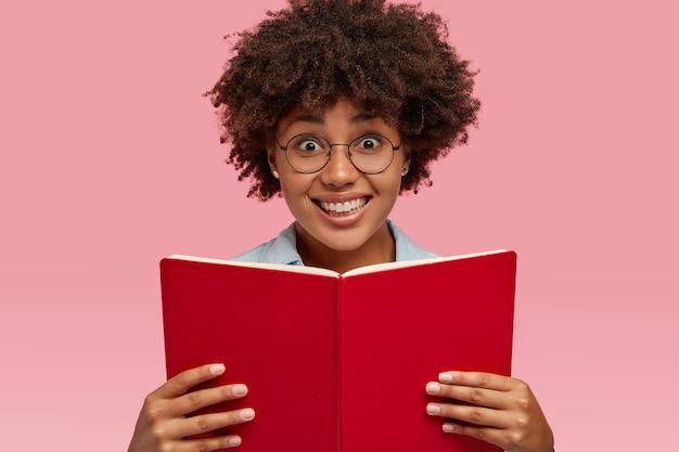 ピンクの壁に隔離された、心地よい表情のかわいい笑顔の女の子の水平方向のショット、教科書を運び、眼鏡をかけ、検査の準備をします。人、民族、リテラシーの概念 無料写真