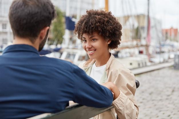 Горизонтальный снимок влюбленной романтической пары, сидящей на скамейке на фоне морского порта, милой беседы Бесплатные Фотографии