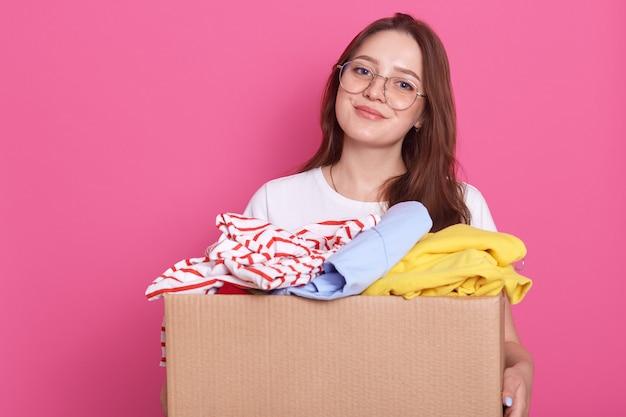 Горизонтальный выстрел улыбается женщина позирует, изолированных на розовый и проведение коробки с многоразовой одежды, одежды для детского дома или бедных людей, очаровательная девушка женщина делает благотворительность. Premium Фотографии