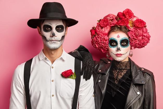 Горизонтальный снимок жуткой пары, одетой к дню мертвых в мексике, одетой в маски черепа, стоящей рядом друг с другом, вместе отмечающей хэллоуин, изолированной на розовом фоне Бесплатные Фотографии