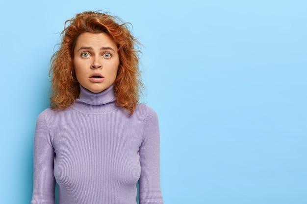기절 한 여자의 가로 샷은 무서운 표정으로 보이는 녹색 눈과 물결 모양의 빨간 머리를 가지고 있습니다. 무료 사진