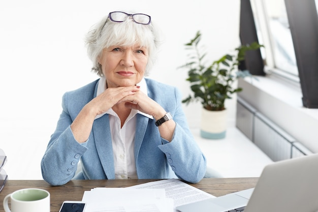 Горизонтальный снимок стильной пожилой женщины-менеджера по недвижимости в красивом синем костюме и очках на голове, с серьезным и уверенным взглядом, держащей руки под подбородком и использующей ноутбук для работы Бесплатные Фотографии