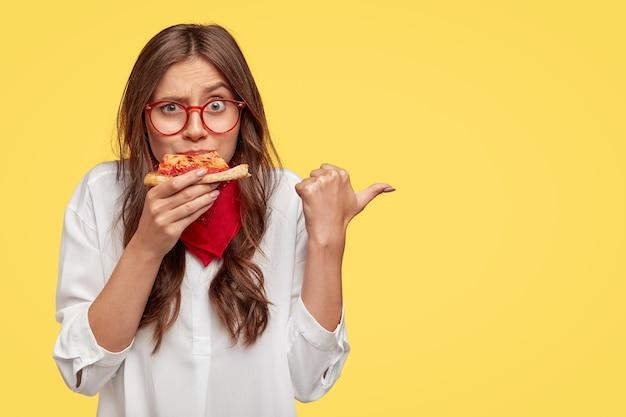 驚いた女性の横のショットは、ファッショナブルな服を着て、ピザのおいしいスライスを食べ、親指で示し、黄色の壁に隔離されたピザ屋にあなたを招待します。人と栄養 無料写真