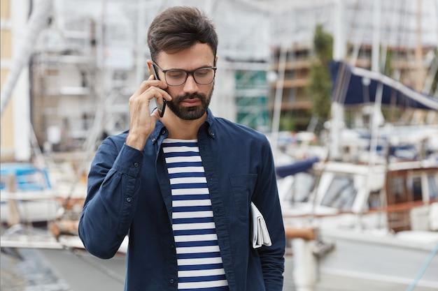 Горизонтальный снимок задумчивого парня, говорящего по телефону Бесплатные Фотографии
