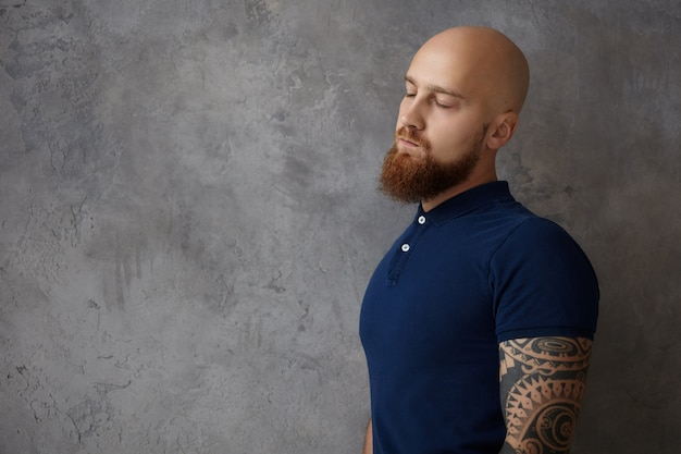Горизонтальный снимок усталого парикмахера с татуировкой на руке и пушистой рыжей бородой, закрывающего глаза, ощущающего сонливость и усталость после тяжелого рабочего дня, позирующего изолированно у пустой стены Бесплатные Фотографии