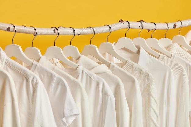Горизонтальный снимок белой женской одежды, висящей на стойках, изолированных на желтом фоне. гримерная с женскими нарядами. Бесплатные Фотографии