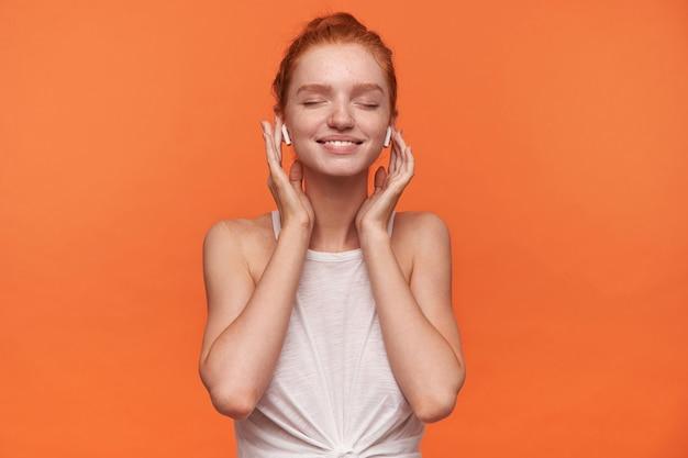 オレンジ色の背景で隔離、結び目でカジュアルな服を着て、目を閉じて彼女のお気に入りの曲を楽しんで、イヤホンで手を維持している赤い髪の若い魅力的な女性の水平方向のショット 無料写真