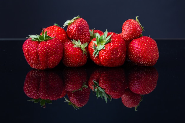 Horizontal shot of a pile of red croatian strawberries on a black reflecting surface Free Photo