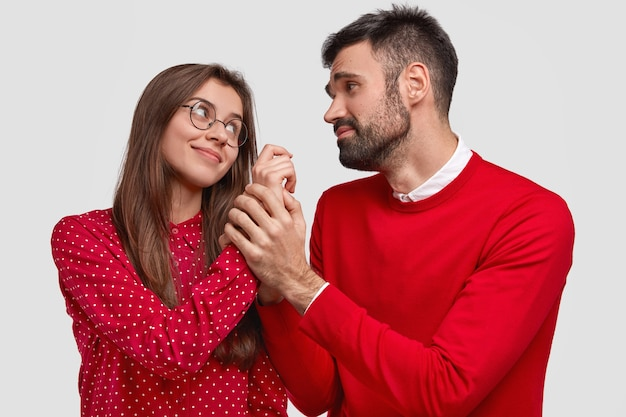 Horizontal shot of pleased woman looks at husband who has pleading expression and holds her hand, wear red clothes, have pleasant talk, isolated over white background. people Free Photo