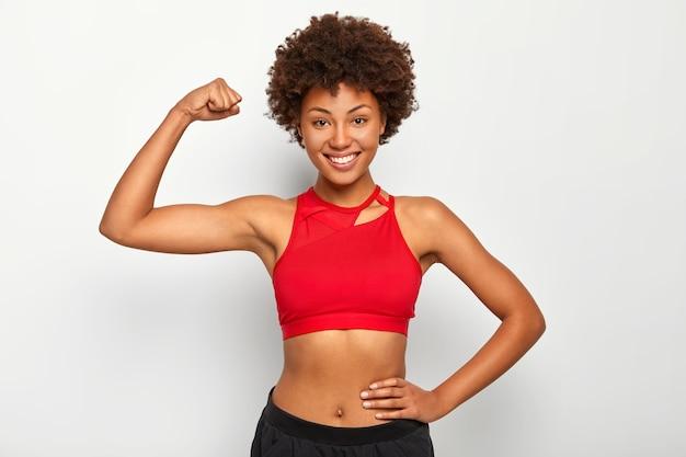 Il colpo orizzontale della donna dalla pelle scura positiva mostra bicipiti, mostra una mano forte, ha una figura snella, indossa reggiseno sportivo, sorride piacevolmente, isolato su sfondo bianco. Foto Gratuite