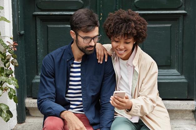 Inquadratura orizzontale di una ragazza dalla pelle piuttosto scura mostra le sue foto sul cellulare al migliore amico Foto Gratuite