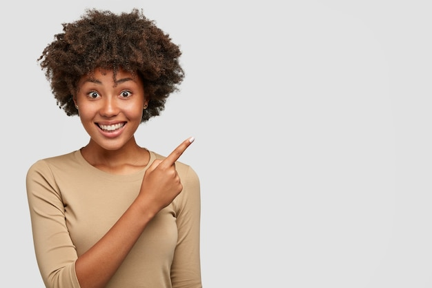 Horizontal shot of pretty dark skinned woman with afro hairstyle, has broad smile, white teeth, shows something nice to friend, points at upper right corner, stands against wall Free Photo