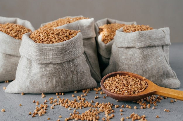 Horizontal shot of roasted buckwheat in sacks and spoon. gluten free grains. harvested uncooked cereals. natural vegan food concept Premium Photo