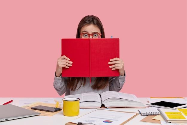 Il colpo orizzontale della signora perplessa spaventata copre il viso con il libro di testo rosso, utilizza le moderne tecnologie Foto Gratuite