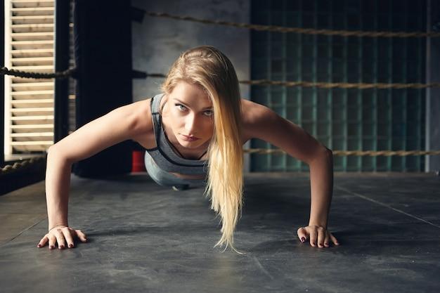 Inquadratura orizzontale di splendida giovane sportiva autodeterminata con capelli tinti sciolti facendo push up piantando le mani ampiamente sul pavimento all'interno del ring di pugilato Foto Gratuite