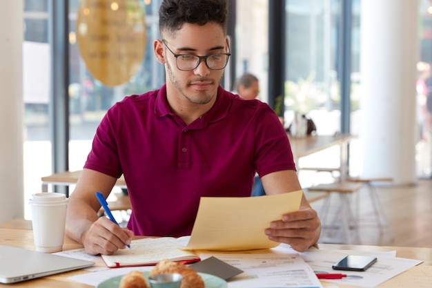 Horizontal shot of serious banker holds paper, writes creative ideas for development of successful banking business, holds pen for writing in notepad, surrounded with modern gadgets in cafeteria Free Photo