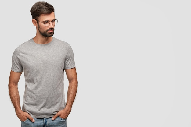 Horizontal shot of serious unshaven male in casual grey t-shirt, keeps hands in pockets, looks aside, thinks about something Free Photo
