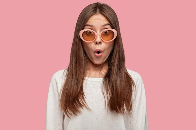Colpo orizzontale di giovane donna stupefatta di fascino con espressione scioccata Foto Gratuite