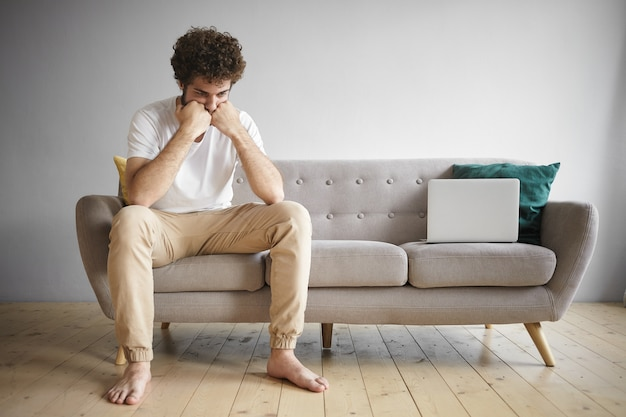 Colpo orizzontale di giovane maschio disoccupato che indossa t-shirt bianca e jeans beige seduto a piedi nudi sul divano da lavoro computer portatile con espressione facciale triste e frustrata, alla ricerca di lavoro online Foto Gratuite