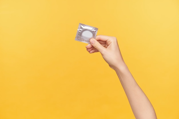 Horizontal shot of young fair-skinned female's hand being raised while holding silver pack with condom. young woman prefer safe sex, posing over orange background Free Photo