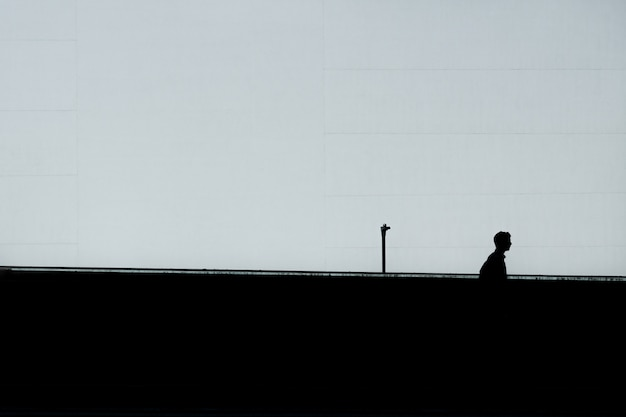 Horizontal silhouette of a lonely male under the clear sky Free Photo