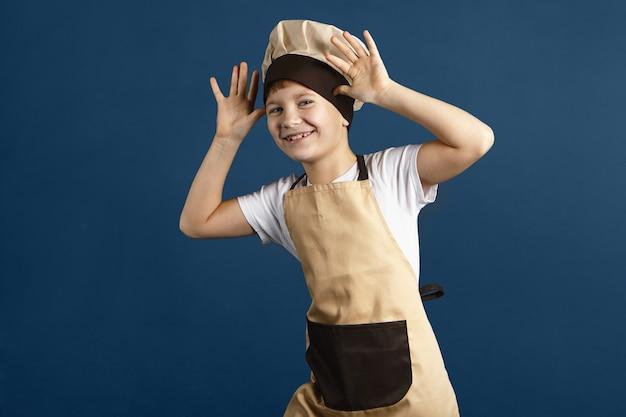Colpo orizzontale dello studio del ragazzino sveglio divertente vestito con cappello da cuoco beige e grembiule che ride, tenendosi per mano alla sua testa, facendo smorfie, stuzzicando qualcuno. bambino maschio che si diverte. concetto di cucina e cibo Foto Gratuite