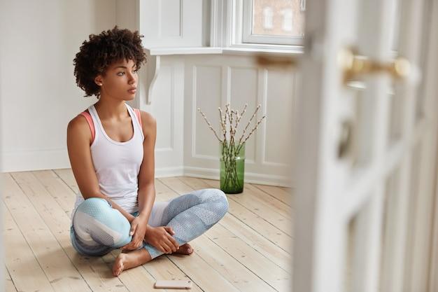 La vista orizzontale della donna contemplativa dalla pelle scura rende le gambe piegate, vestite in abiti casual, ha riposo dopo l'allenamento mattutino Foto Gratuite