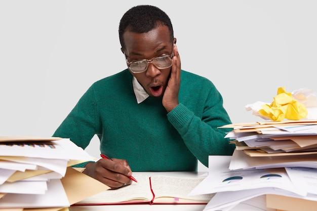 驚いた黒人男性の水平方向のビューは、ドキュメントを処理し、メモ帳にメモを書き留め、顔の表情を馬鹿にし、大きな眼鏡をかけています 無料写真