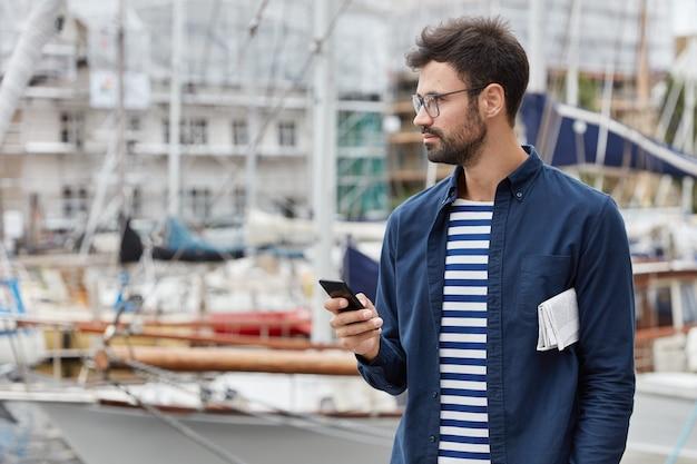 Горизонтальный вид на вдумчивые блоги фрилансера в социальных сетях, держит современный мобильный телефон Бесплатные Фотографии