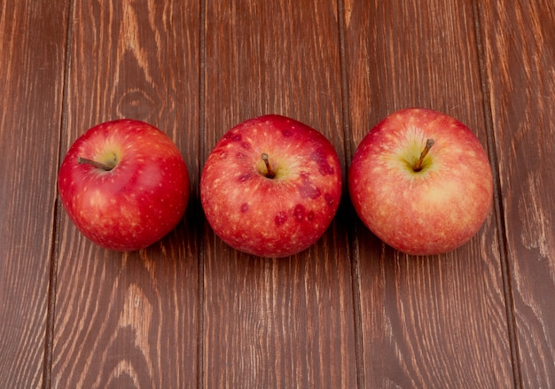 Horizontal view of red apples on wooden background Free Photo