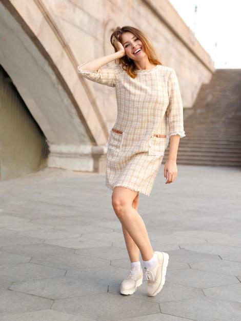Горизонтальный вид. молодая привлекательная женщина с рыжими волосами, носить бежевое элегантное платье, позирует на улице. красивая девушка гуляет по улице. Premium Фотографии