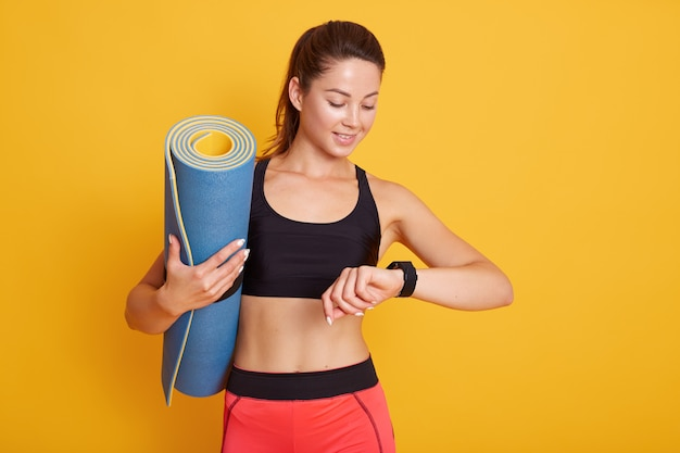 Horozontal shot of fitness woman after workout session checks results on smartwatch in fitness app, female with pefect body isolated over yellow background. healthy lifestyle and sport concept. Premium Photo